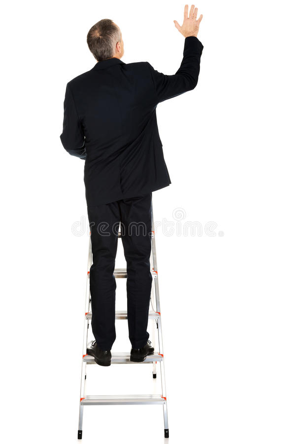 Back view of businessman climbing ladder royalty free stock images