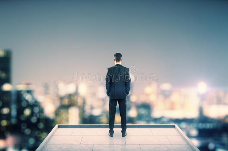 Businessman on rooftop. Back view of businessman looking into the distance on rooftop with blurry night city view. Copy space. Success, vision and future concept royalty free stock photography