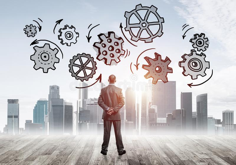 Cogwheel engine drawn on screen as symbol for teamwork and cooperation. Back view of businessman looking at modern city and drawn gear mechanism royalty free stock photo