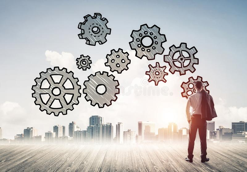 Cogwheel engine drawn on screen as symbol for teamwork and cooperation. Back view of businessman looking at modern city and drawn gear mechanism stock photos
