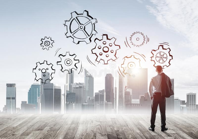 Cogwheel engine drawn on screen as symbol for teamwork and cooperation. Back view of businessman looking at modern city and drawn gear mechanism stock photography