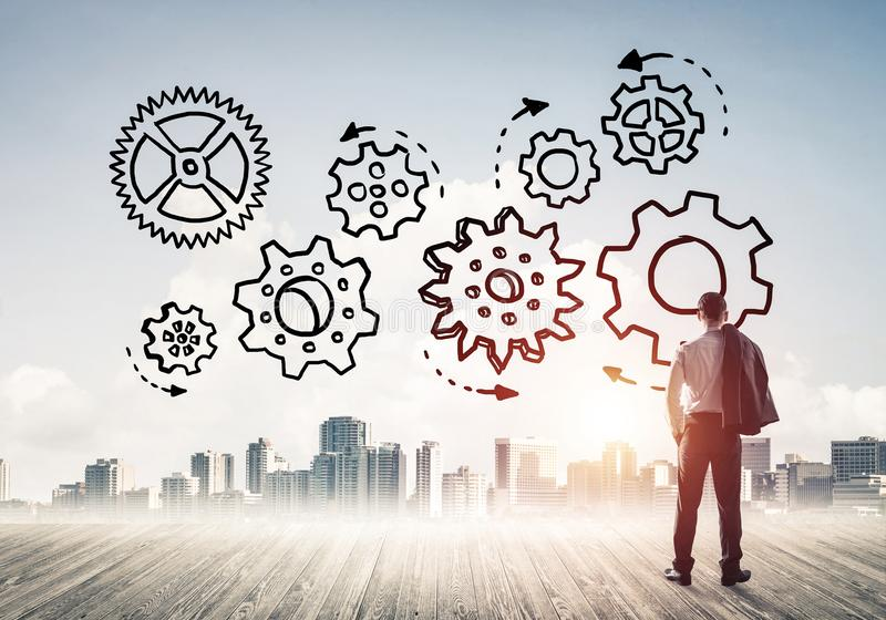 Cogwheel engine drawn on screen as symbol for teamwork and cooperation. Back view of businessman looking at modern city and drawn gear mechanism stock image