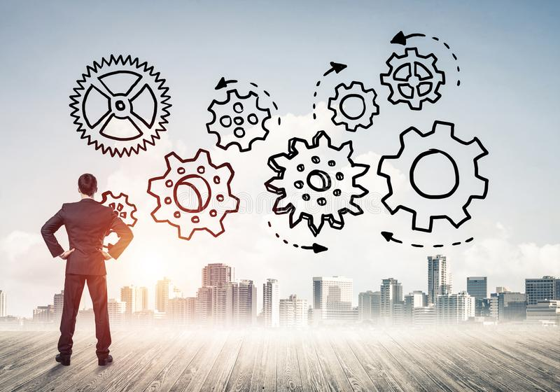 Cogwheel engine drawn on screen as symbol for teamwork and cooperation. Back view of businessman looking at modern city and drawn gear mechanism royalty free stock image