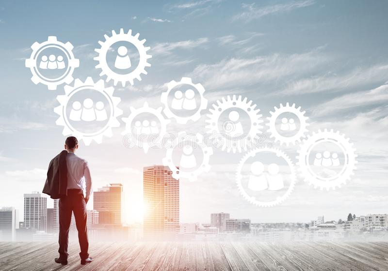 Social connection concept drawn on screen as symbol for teamwork and cooperation. Back view of businessman looking at modern cityscape and gear connection idea royalty free stock image