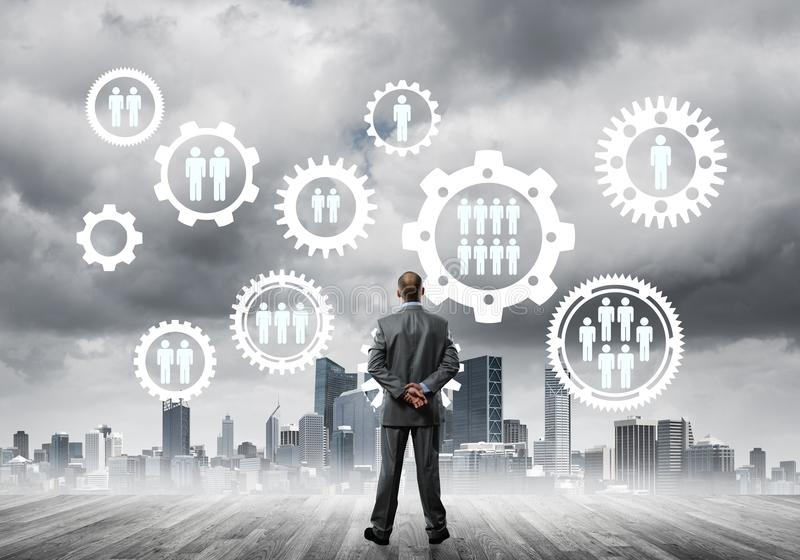 Social connection concept drawn on screen as symbol for teamwork and cooperation. Back view of businessman looking at modern cityscape and gear connection idea stock photo