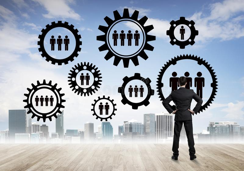 Social connection concept drawn on screen as symbol for teamwork and cooperation. Back view of businessman looking at modern cityscape and gear connection idea stock photography