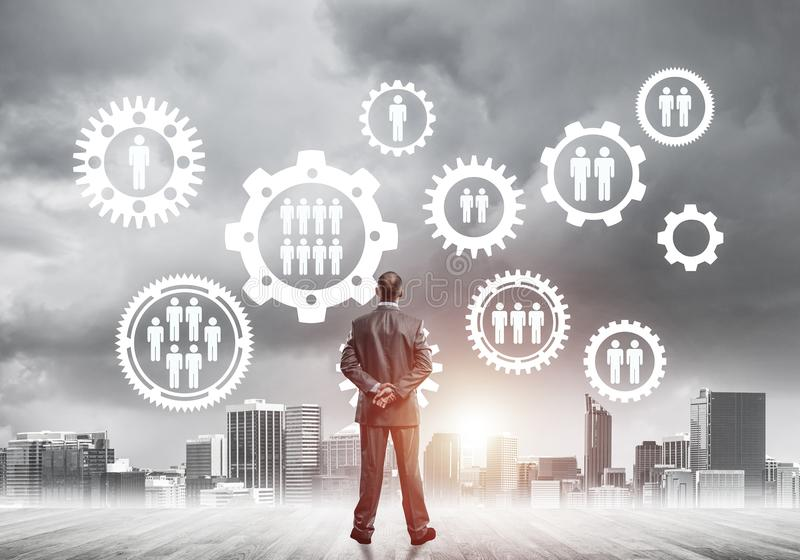 Social connection concept drawn on screen as symbol for teamwork. Back view of businessman looking at modern cityscape and gear connection idea royalty free stock image