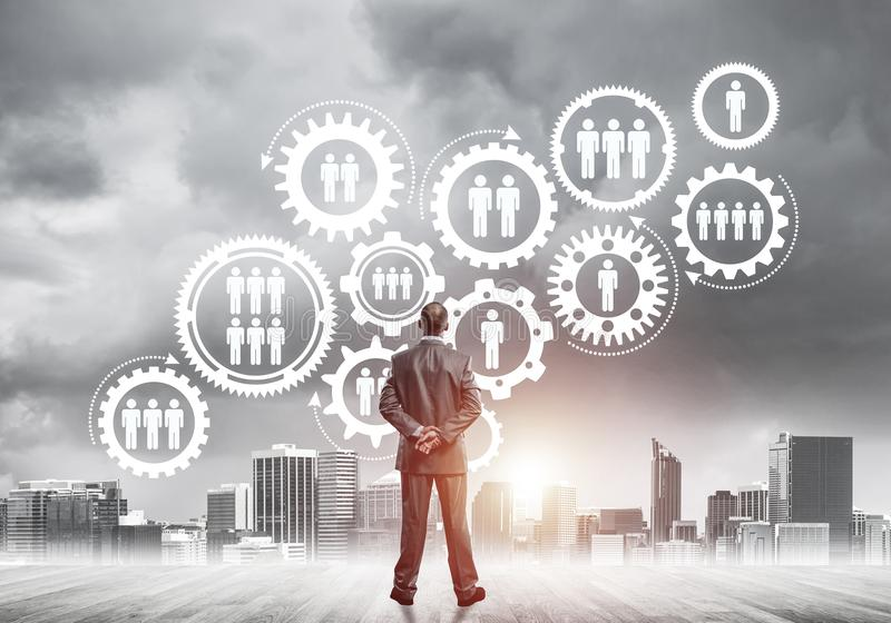 Social connection concept drawn on screen as symbol for teamwork. Back view of businessman looking at modern cityscape and gear connection idea stock photos