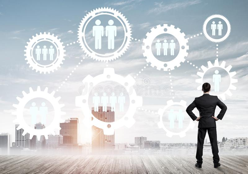 Social connection concept drawn on screen as symbol for teamwork and cooperation. Back view of businessman looking at modern cityscape and gear connection idea royalty free stock photo