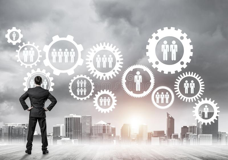 Social connection concept drawn on screen as symbol for teamwork. Back view of businessman looking at modern cityscape and gear connection idea royalty free stock images