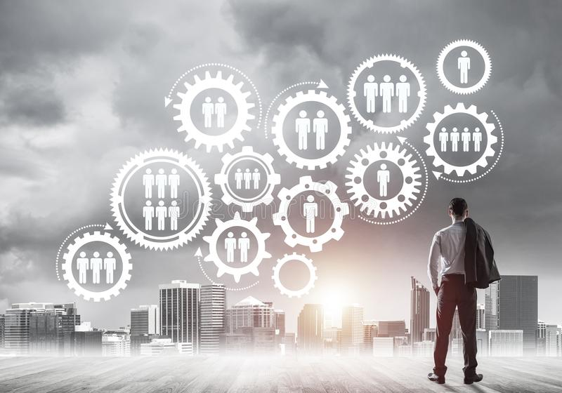 Social connection concept drawn on screen as symbol for teamwork. Back view of businessman looking at modern cityscape and gear connection idea stock photography