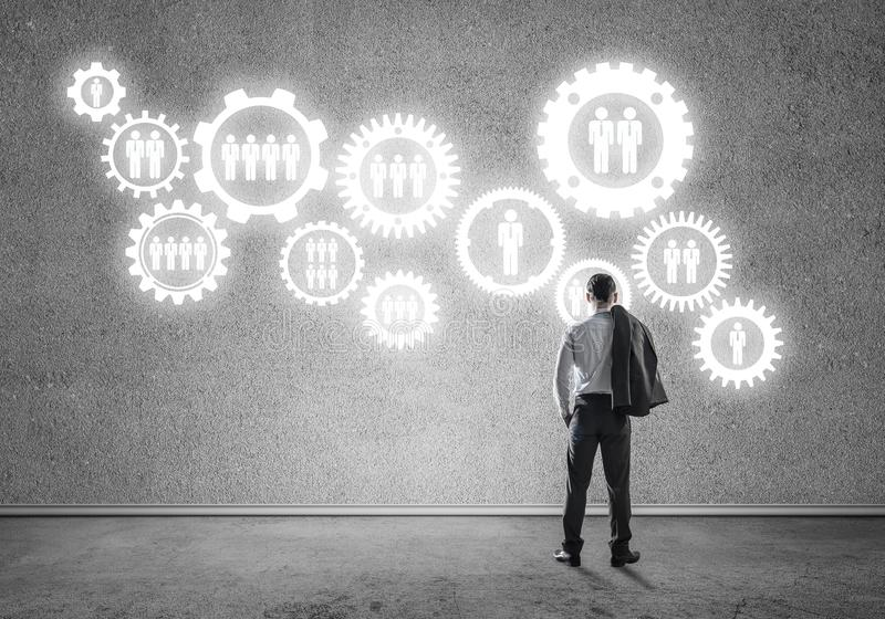 Cogwheel engine drawn on concrete wall as symbol for teamwork an. Back view of businessman looking at wall with drawn gear mechanism stock photo