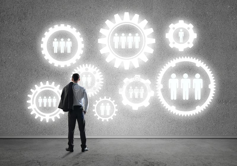 Cogwheel engine drawn on concrete wall as symbol for teamwork and cooperation. Back view of businessman looking at wall with drawn gear mechanism stock images