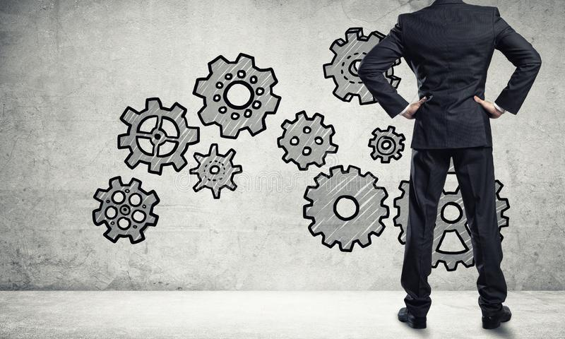 Teamwork concept drawn on wall. Back view of businessman looking at wall with drawn gear mechanism royalty free stock photos
