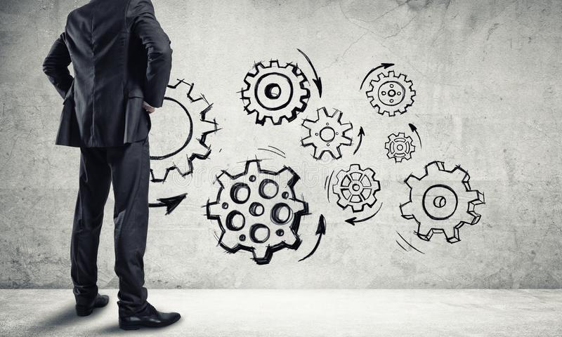 Teamwork concept drawn on wall. Back view of businessman looking at wall with drawn gear mechanism stock image