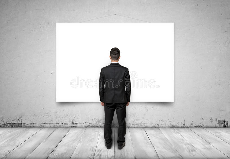 Back view of businessman looking at white empty canvas on concrete wall stock photos