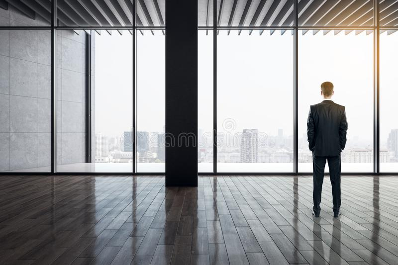Businessman in modern office. Back view of businessman standing in modern office interior with panoramic city view, reflections on wooden floor and daylight stock photos