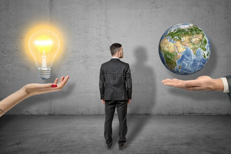 Back view of businessman standing between two big hands, woman`s hand levitating lightbulb, man`s hand levitating little royalty free stock images