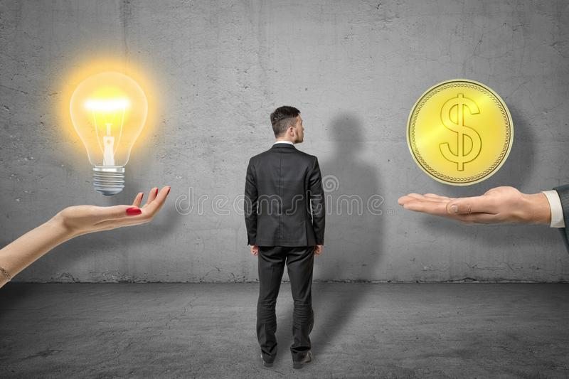Back view of businessman standing between woman`s hand facing up with lit electric bulb above it and man`s palm with big stock photography