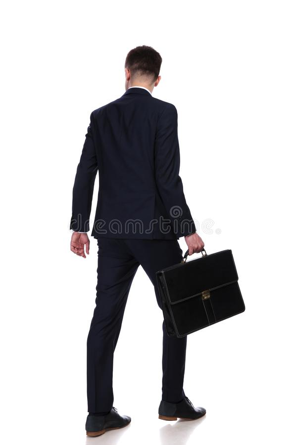Back view of businessman with suitcase walking stock image