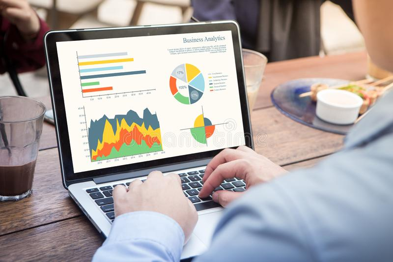 Back view of businessman using laptop analyzing statistics data on laptop screen, working with graphs charts online. stock photography