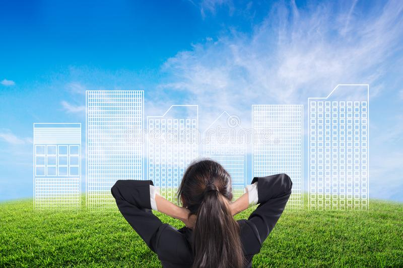 Back view of businesswoman looking sketches of construction project on nature background. stock image