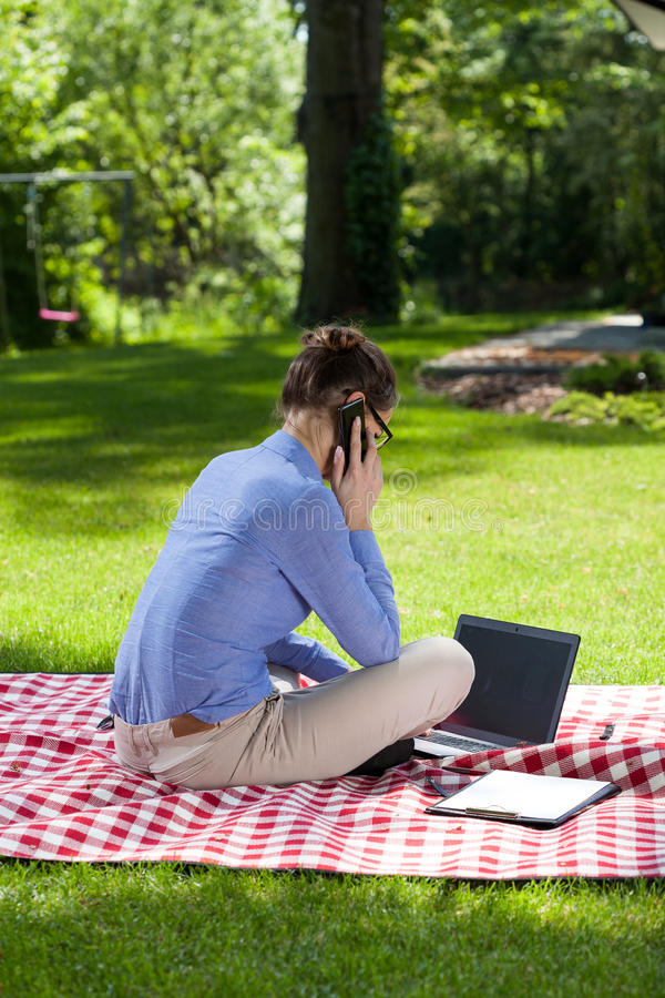 Back view of a busy woman talking on mobile phone in the garden royalty free stock photo