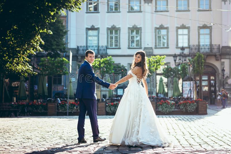 Back view of the cheerful adorable newlywed couple holding hands in the street at the background of the beautiful house. stock photo