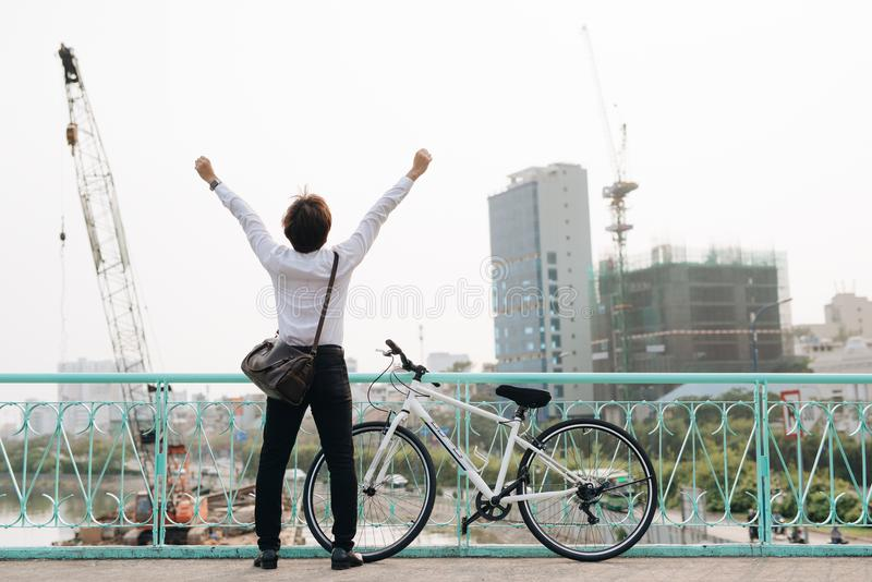 Back view of cheerful man with hands up with bicycle royalty free stock images