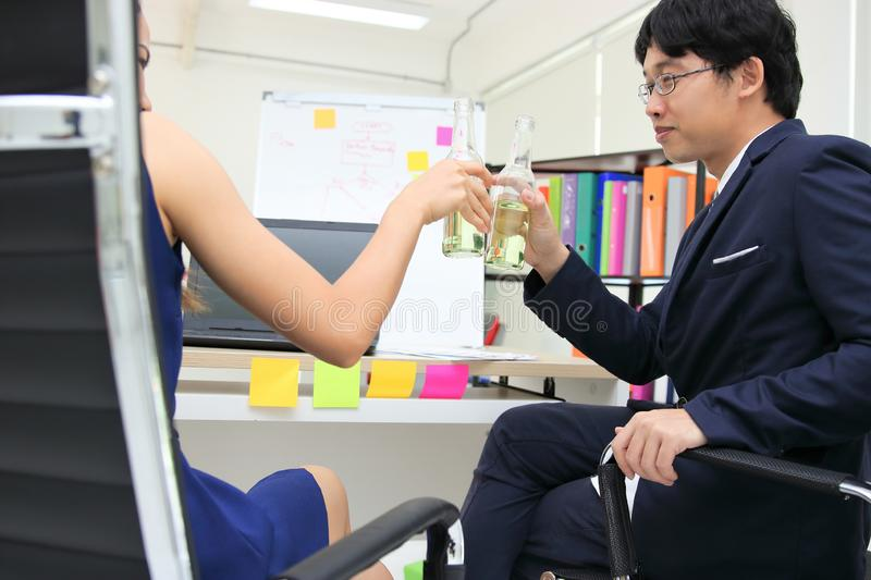 Back view of cheerful young Asian business partners clinking bottle of wine in office. Successful and celebration concept stock image