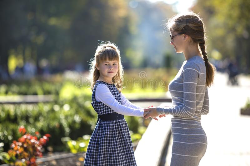 Back view of child girl and mother in dresses together holding hands on warm day outdoors on sunny background stock photo