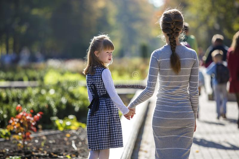 Back view of child girl and mother in dresses together holding hands on warm day outdoors on sunny background stock image