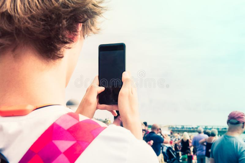 Back view close up young man filming video or taking photo pictures on his mobile phone during outdoor event. Selective focus. Cop stock photos