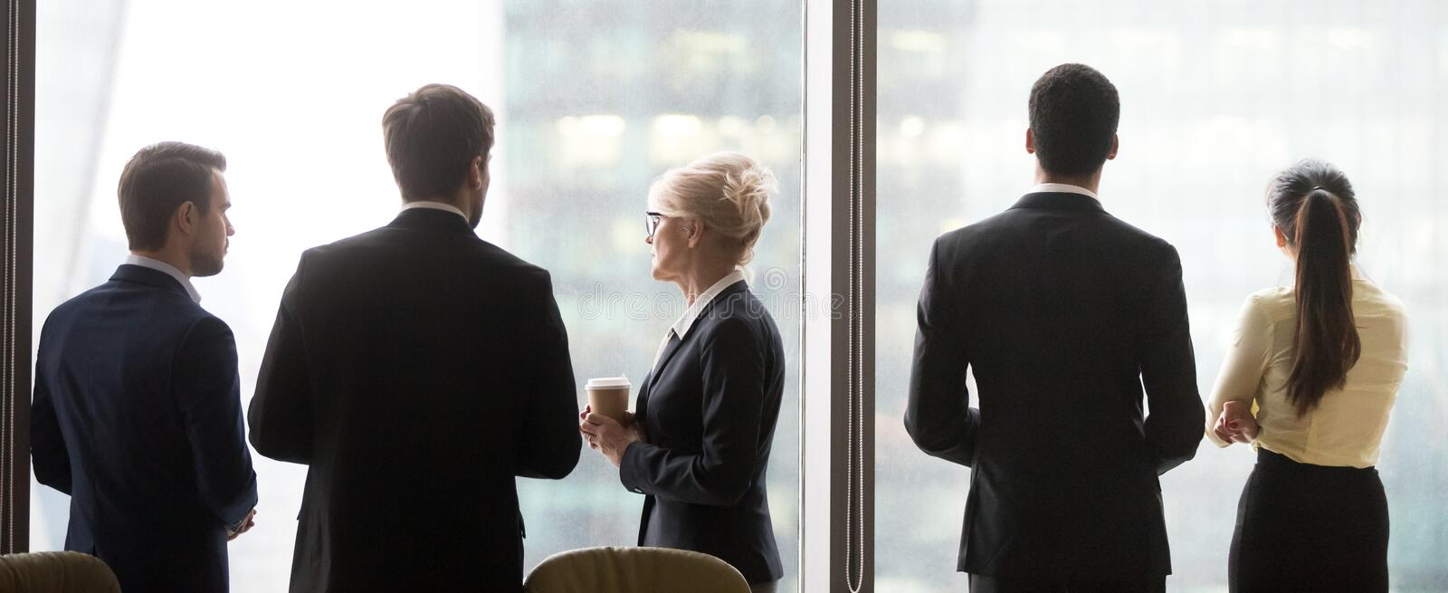 Back view of colleagues standing near window enjoying coffee bre stock photos