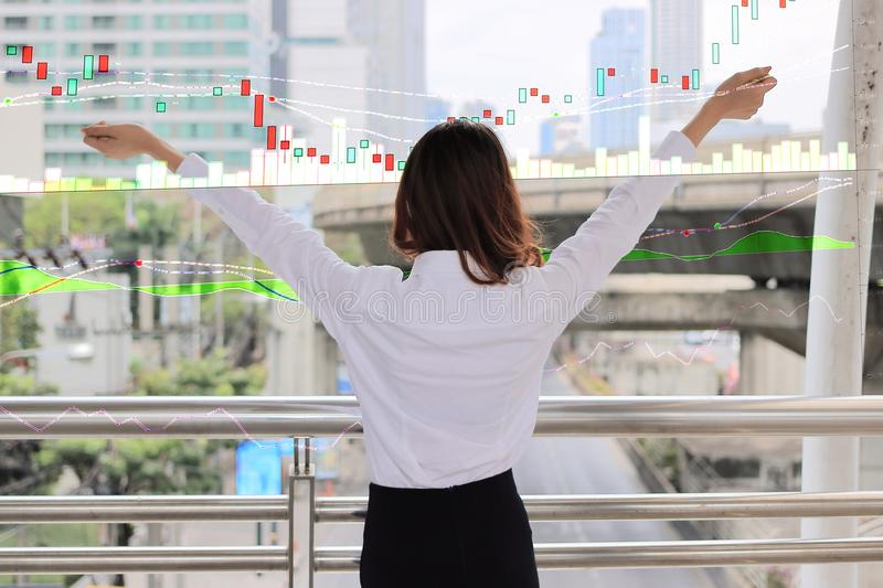 Back view of confident Asian business woman raising hand and looking far away in urban building city against growth stock chart gr. Aphic background stock images