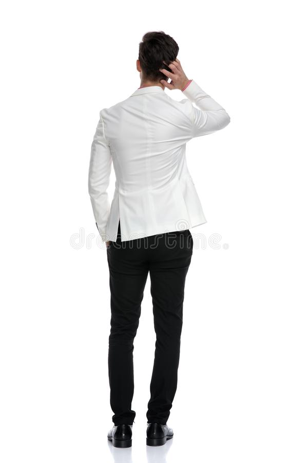 Back view of a confused business man scratching his head royalty free stock photography