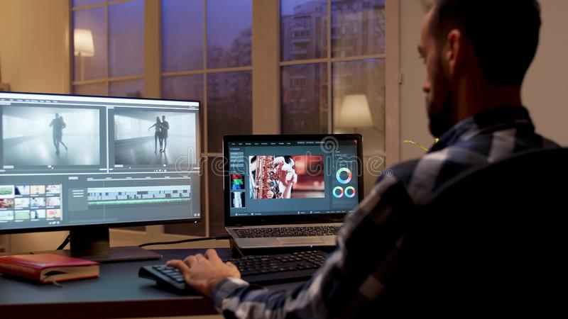 Back view of content creator working in home office. During night time. Video editor in home office stock photo