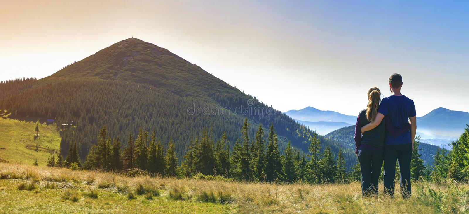 Back view of couple athletic boy and blond girl standing together embraced enjoying breathtaking view of magnificent Carpathian mo stock photo