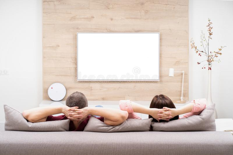Back view of couple man and woman resting in apartment, sitting on sofa together and watching TV. Back view of couple men and women resting in apartment, sitting stock photos
