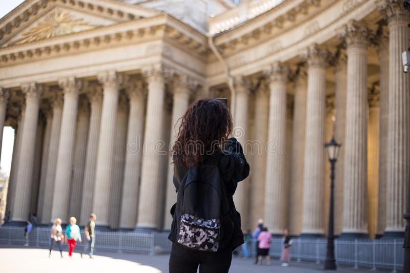 Back view of a curly woman who travels, doing a pictures with her mobile phone of a cathedral, blurred background. stock image