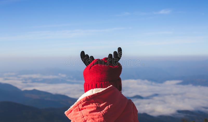 Cute asian child girl wearing sweater and warm hat looking to beautiful mist and mountain nature in winter stock image