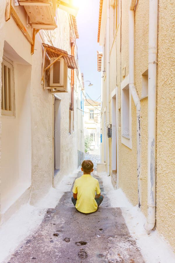 Back view of cute boy sitting on the steps on street in old greece town, Crete island, Greece. Summer landscape. Back view of cute boy sitting on the steps on royalty free stock photo