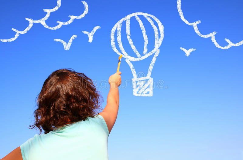 Back view of cute kid imagine and painting air baloon in the sky stock photo
