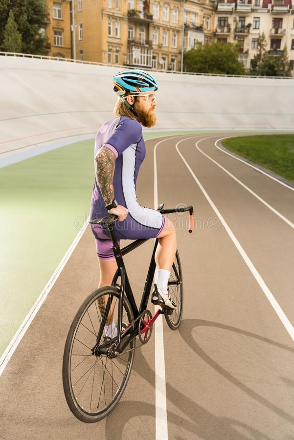Cyclist on cycle race track. Back view of cyclist in sportswear and helmet with bicycle on cycle race track royalty free stock images