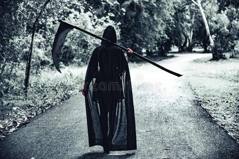 Back view of demon witch with reaper and red blood on hands walk stock photo