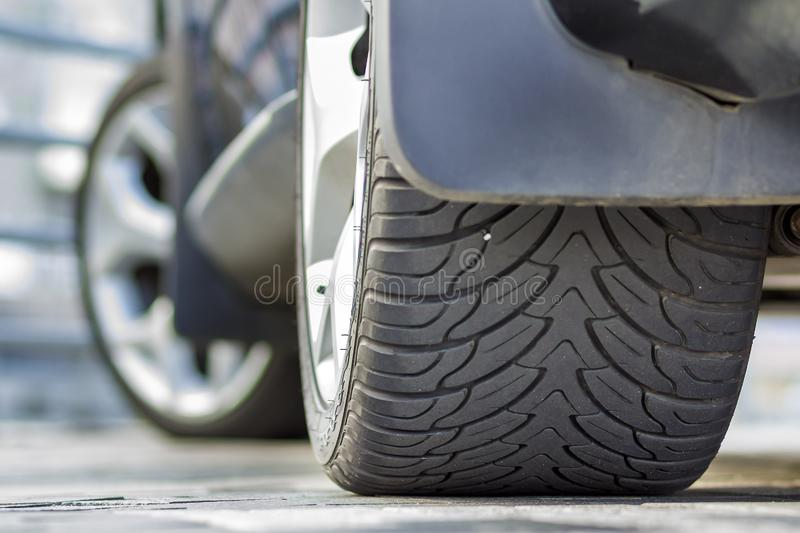 Back view detail part of black shiny luxurious car tire parked on pavement background on bright sunny day. Transportation, stock photos