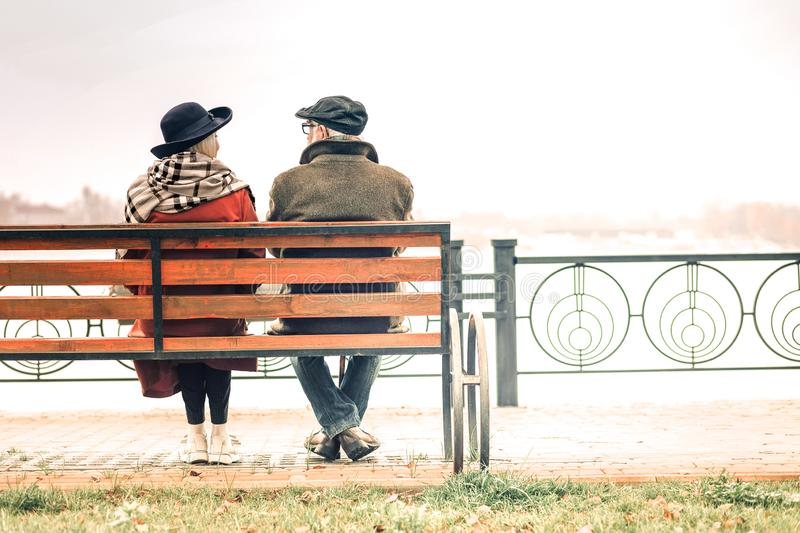 Back view of a elderly couple relaxing on bench in park royalty free stock images