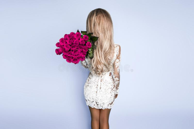 Back view of elegant beautiful woman is wearing white fashion dress is holding big bouquet of 101 red roses - Image royalty free stock image