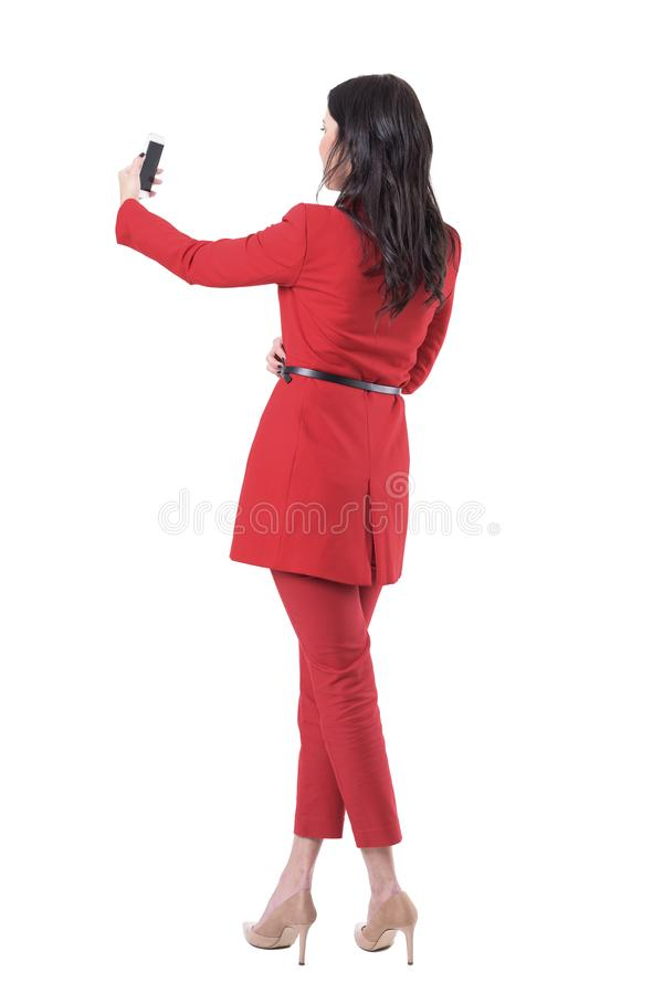 Back view of elegant business woman in red suit taking selfie photos with smart phone. royalty free stock images