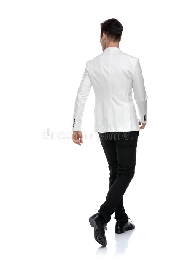 Back view of elegant businessman walking and looking to side stock photos